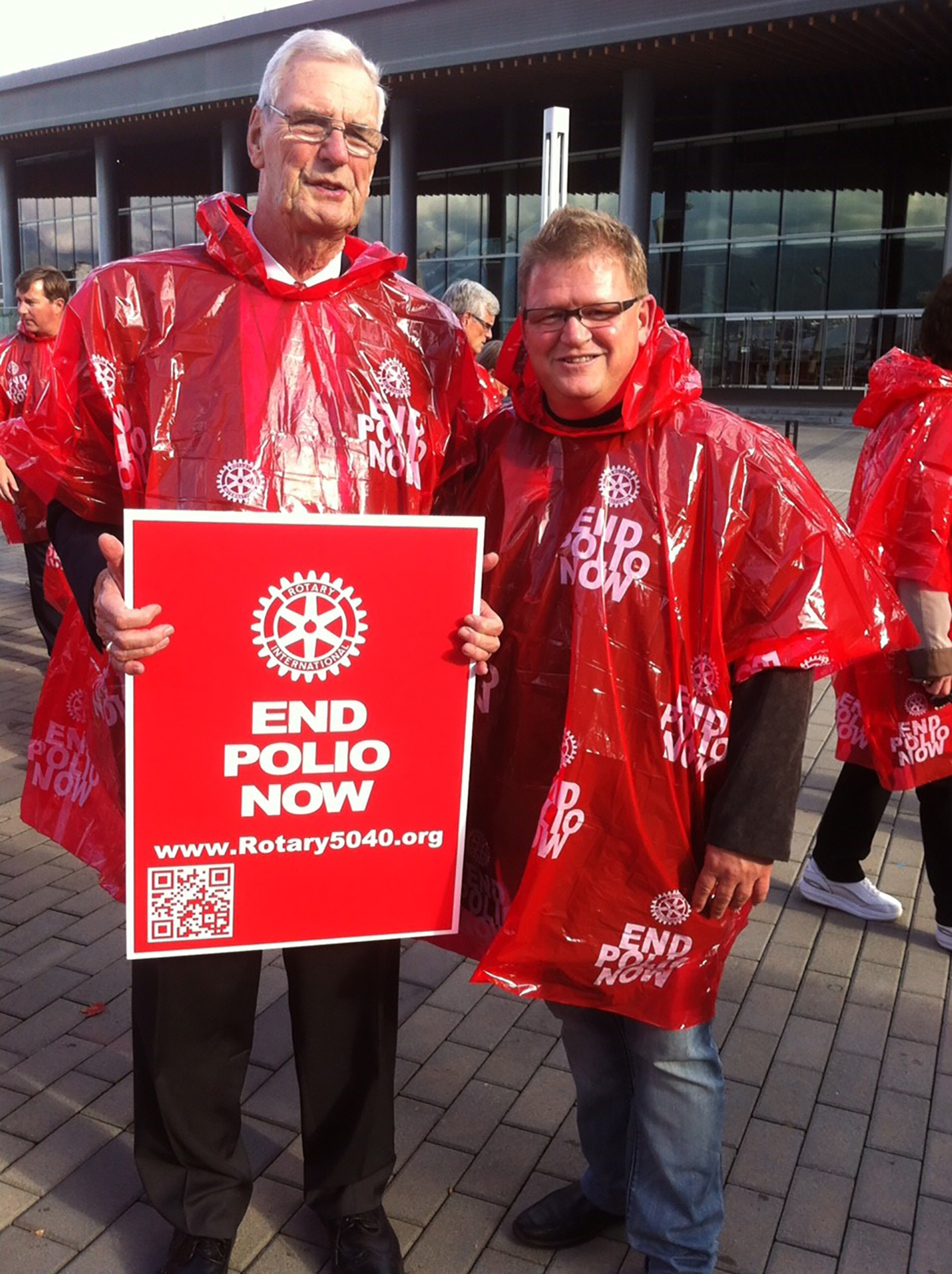 Bob Scott and Michael Kinsey don red ponchos to raise awareness on World Polio Day.